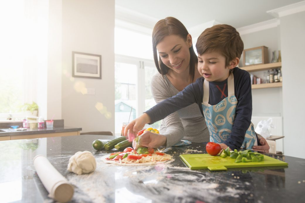 Mother and son preparing pizza together in kitchen